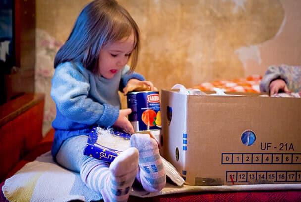 Liten flicka öppnar julpaket i Lettland